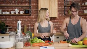 Happy young woman feeding her boyfriend with paprika pepper while he cutting vegetables for salad. Healthy eating, diet stock footage