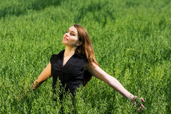 Happy young woman in a field. Royalty Free Stock Images