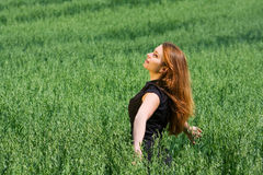 Happy young woman in a field. Royalty Free Stock Image