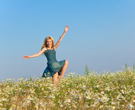 The happy young woman in the field of camomiles Stock Photo