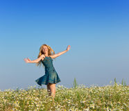 The happy young woman in the field of camomiles Stock Image
