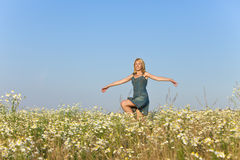 The happy young woman in the field  of camomiles Stock Images