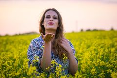 Young woman in a field of oil rapeseed in bloom in sunset. Freedom and ecology concept. Stock Images