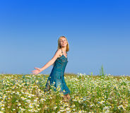 Happy young woman in the field of chamomiles Stock Images