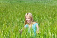 The happy young woman in the field of green ears Royalty Free Stock Photos