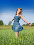 Happy young woman in the field of green ears Stock Photography