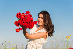 Happy young woman in the field with a poppies bouquet. Stock Image