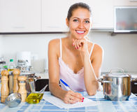 Happy young woman filling papers Royalty Free Stock Image