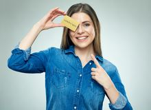 Happy young woman finger pointing to golden credit card. Royalty Free Stock Image