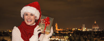Happy young woman in Florence, Italy shaking Christmas gift Stock Images
