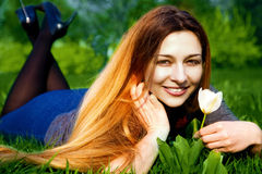 Happy young woman and flower in fresh grass Royalty Free Stock Photos