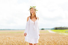 Happy young woman in flower wreath on cereal field Royalty Free Stock Image