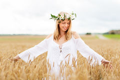 Happy young woman in flower wreath on cereal field Stock Photos