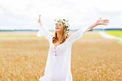 Happy young woman in flower wreath on cereal field Stock Image