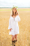 Happy young woman in flower wreath on cereal field Stock Photography