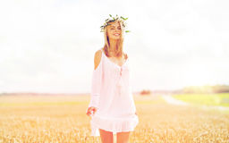 Happy young woman in flower wreath on cereal field Stock Images