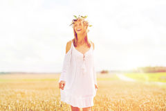 Happy young woman in flower wreath on cereal field Stock Photo