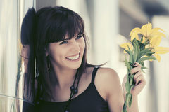 Happy young woman with flowers in city street Royalty Free Stock Images