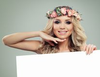 Happy Young Woman with Flowers Hairstyle Holding. White Banner for Text. Blonde Beauty. Fashion Model with Long Permed Curly Hair and Perfect Makeup. Spring Stock Photo