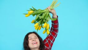 Young woman with flowers tulips in hands on a blue background. Happy Young woman with flowers tulips in hands on a blue background stock footage