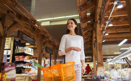 Happy young woman with food basket in market Royalty Free Stock Photography