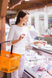 Happy young woman with food basket in market Royalty Free Stock Photos