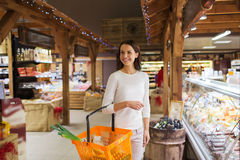 Happy young woman with food basket in market Stock Images