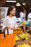 Happy young woman with food basket in market Stock Photos