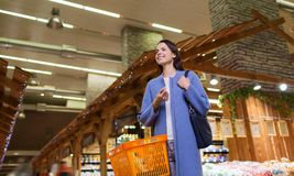 Happy young woman with food basket in market Stock Photo