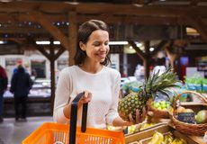 Happy young woman with food basket in market Royalty Free Stock Images