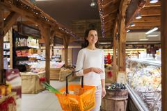 Happy young woman with food basket in market Royalty Free Stock Image