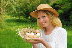 Happy young woman and fresh eggs Stock Image