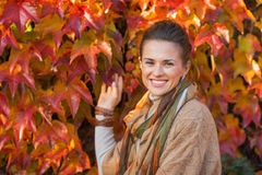 Happy young woman in front of autumn foliage Stock Image