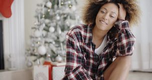 Happy young woman in front of a Christmas tree. Happy young African woman relaxing on the floor in front of a Christmas tree in her living room at home smiling stock video