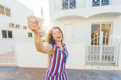 Happy young woman In Front of New Home with New House Keys. Young woman In Front of New Home with New House Keys Stock Photography