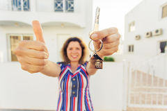 Happy young woman In Front of New Home with New House Keys. Young woman In Front of New Home with New House Keys Stock Photos