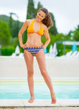 Happy young woman in front of pool Royalty Free Stock Photos