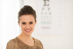 Happy young woman in front of Snellen chart Stock Image
