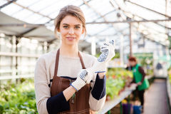 Happy young woman gardener in garden gloves and apron Stock Photo