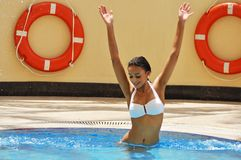 Happy young woman getting fun in a swimming pool Stock Photography