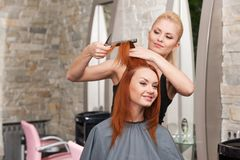Happy young woman getting a new haircut. Royalty Free Stock Photography