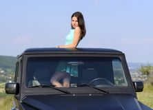 Happy young woman getting out the car's sunroof Royalty Free Stock Images