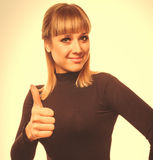 Happy young woman girl shows positive studio sign thumbs yes, in Royalty Free Stock Image