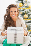 Happy young woman giving christmas present box Stock Photography