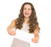 Happy young woman giving envelope Stock Photo