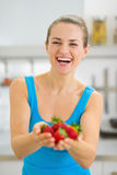 Happy young woman giving strawberries Stock Image