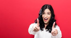 Happy young woman giving thumbs up Royalty Free Stock Photos