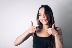Happy young woman giving thumbs up. stock photos