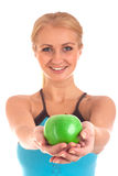 Happy young woman giving you an apple Royalty Free Stock Photography