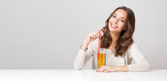 Happy young woman with glass of fruit juice. Royalty Free Stock Photo